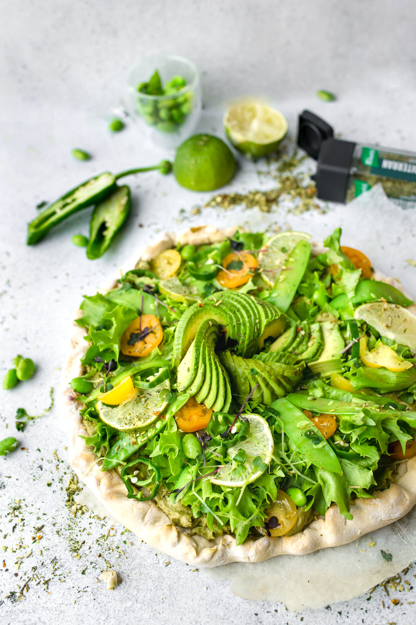 Frühlingshafte vegane Pizza mit Guacamole Topping